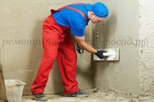 штукатур выравнивает стену